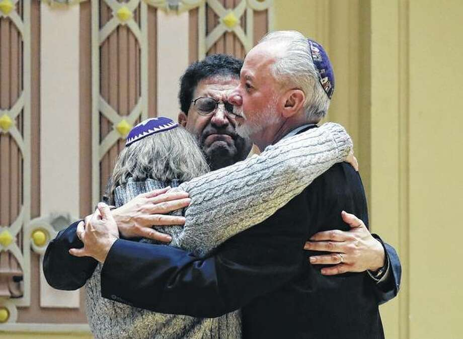 Rabbi Jeffrey Myers (right) of Tree of Life/Or L'Simcha Congregation hugs Rabbi Cheryl Klein (left) of Dor Hadash Congregation and Rabbi Jonathan Perlman during a community gathering in the aftermath of a deadly shooting at the Tree of Life Synagogue in Pittsburgh. As the Jewish community grieved, Myers took a leading role during public memorials and presided over seven funerals in the space of less than a week. Photo: Matt Rourke | AP