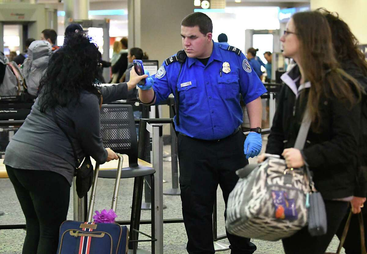 A Transportation Security Administration agent checks a passenger's phone for pre-check at the Albany International Airport on Friday, Dec. 28, 2018 in Colonie, N.Y. (Lori Van Buren/Times Union)