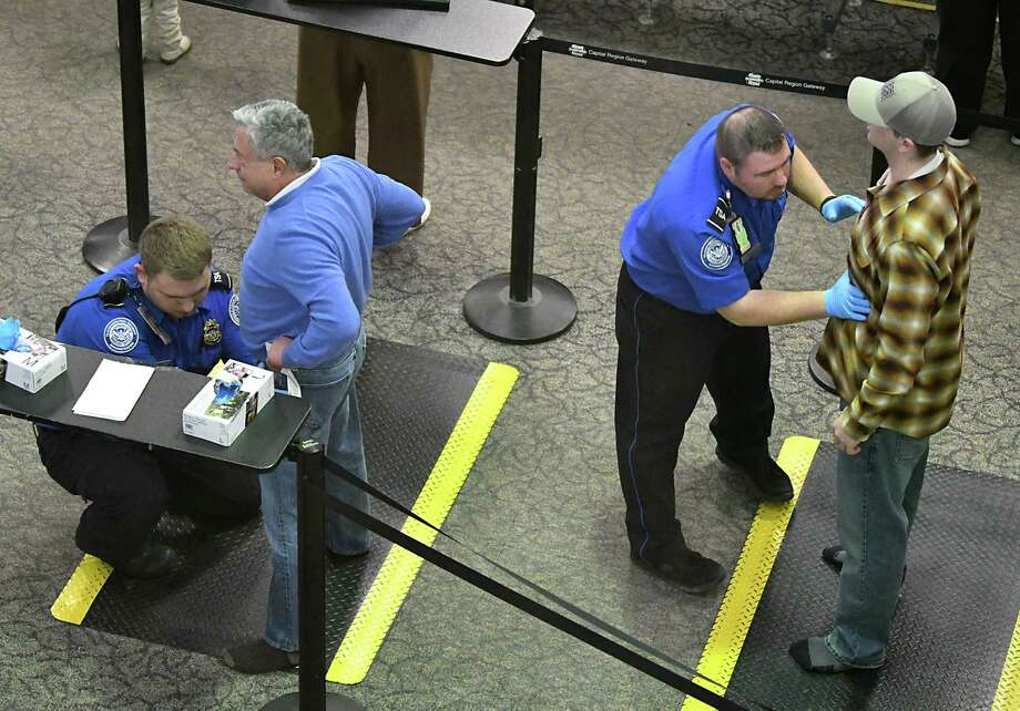 Transportation Security Administration agents check passengers at the security checkpoint at the Albany International Airport on Friday, Dec. 28, 2018 in Colonie, N.Y. (Lori Van Buren/Times Union) Photo: Lori Van Buren, Albany Times Union / 20045821A
