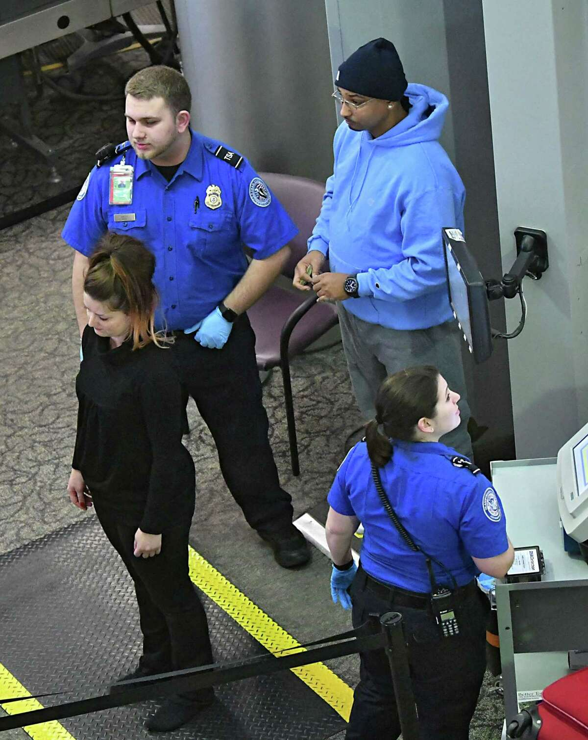 Transportation Security Administration agents check passengers at the security checkpoint at the Albany International Airport on Friday, Dec. 28, 2018 in Colonie, N.Y. (Lori Van Buren/Times Union)