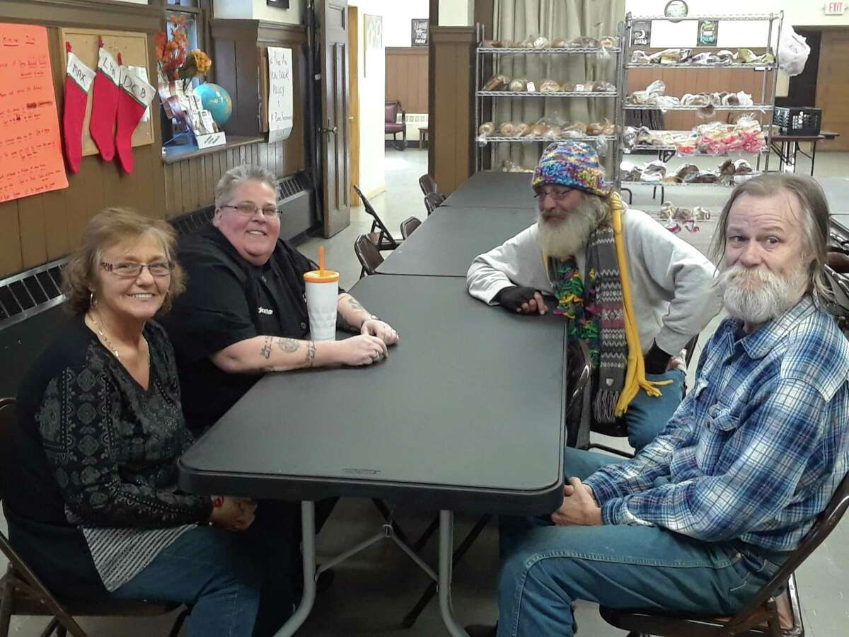 Lisa Hageman, director of the Community Soup Kitchen at Trinity Church in Torrington, chats with clients Sally Doyle, Dave Boido and Bill Bunnell before lunchtime.