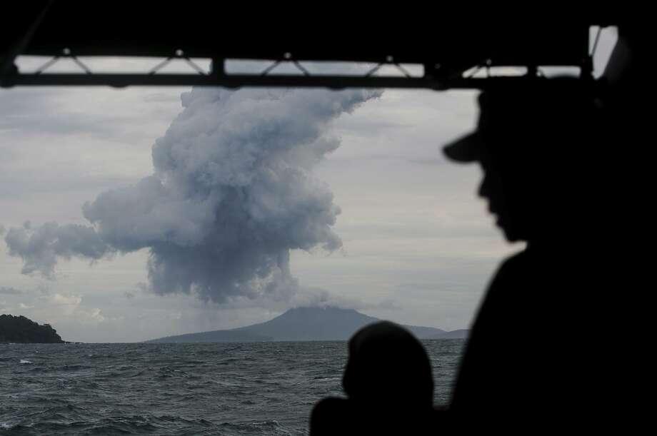 Navy personnel watch as Anak Krakatau spews sulphur and ash in the waters of Sunda Strait. Photo: Fauzy Chaniago / Associated Press