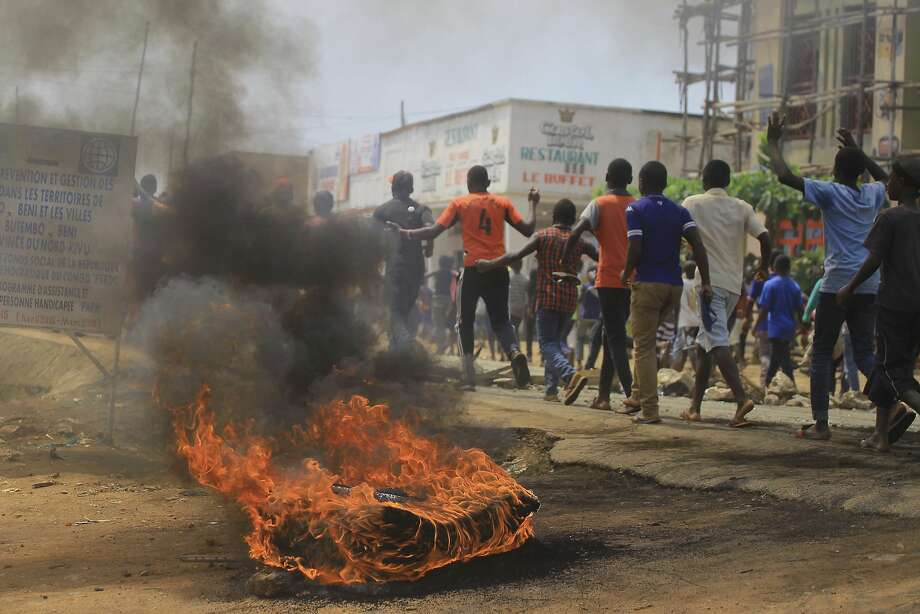 Protesters walk past a burning tire in the eastern town of Beni. They are angry over the decision that they will not be able to vote in Sunday's presidential election until March 2019. Photo: Al-Hadji Kudra Maliro / Associated Press