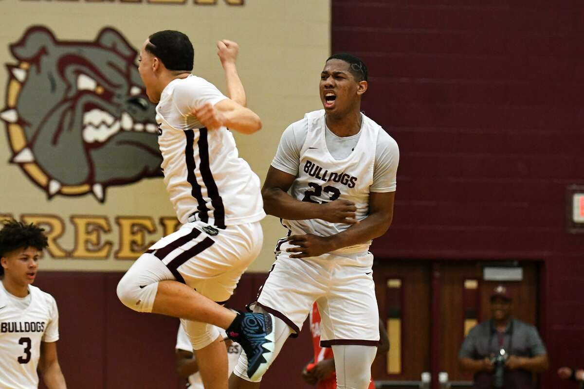 Summer Creek senior guard Dylan Phillips (23) and junior guard Jayden Moore, left, celebrate the Bulldog's win over Atascocita in their District 22-6A matchup at Summer Creek High School on Dec. 21, 2018.