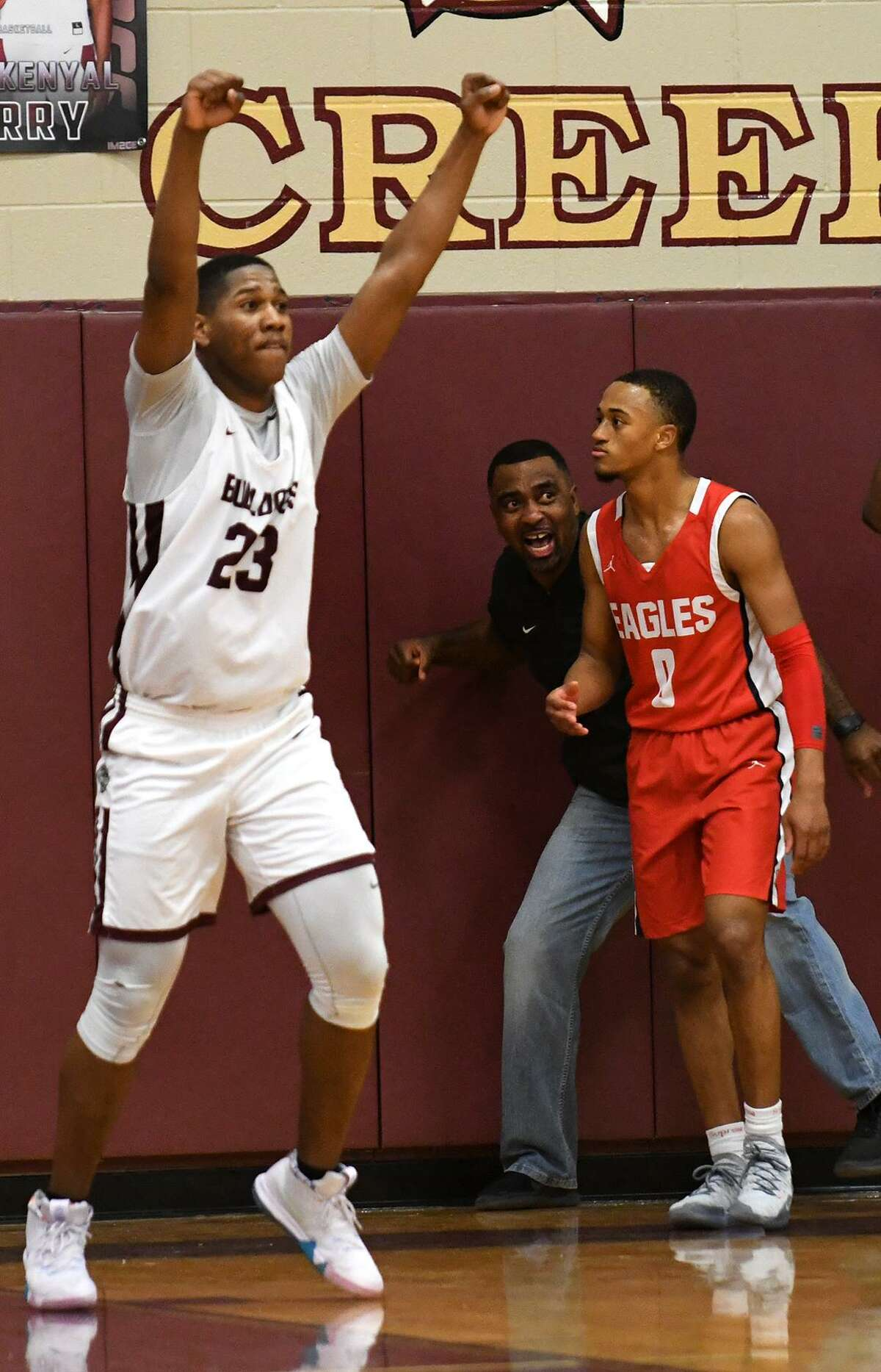 Summer Creek senior guard Dylan Phillips (23) celebrates the Bulldog's win over Joe Rollins (0) and the Atascoita Eagles in their District 22-6A matchup at Summer Creek High School on Dec. 21, 2018.