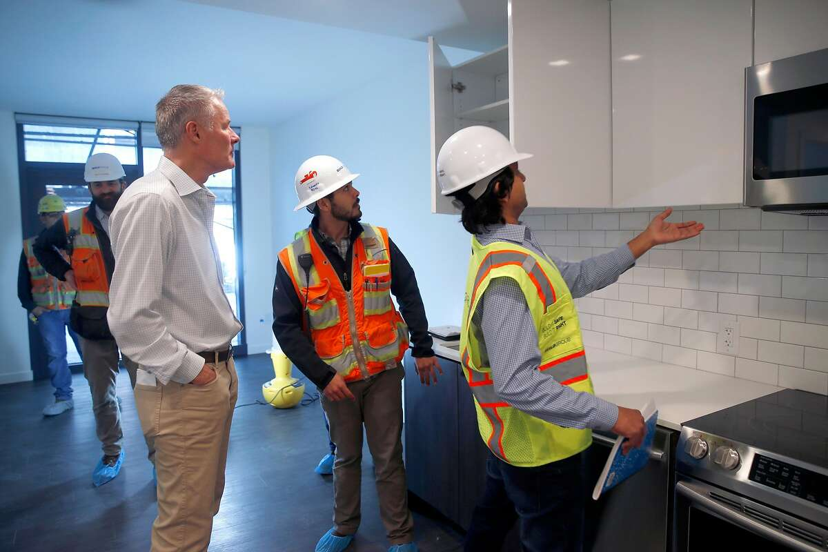 Mark Conroe (left) views kitchen cabinets in a residential building under construction at Market and Valencia streets in San Francisco, Calif. on Tuesday, Dec. 18, 2018. Conroe's Presidio Development Partners company is developing a 160-unit apartment project on the former site of the Flax Art store.