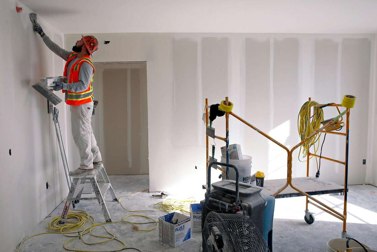 Alonso Gutierrez prepares an apartment for a final coat of paint in a residential building under construction at Market and Valencia streets in San Francisco, Calif. on Tuesday, Dec. 18, 2018. Mark Conroe's Presidio Development Partners company is developing a 160-unit apartment project on the former site of the Flax Art store.