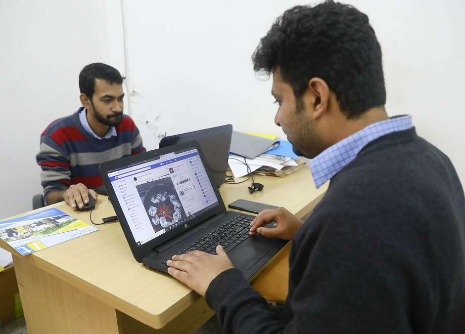 An employee at a photography institute checks his Facebook account in Dhaka, Bangladesh. Facebook shut down some sites spreading false information about the Bangladesh opposition days before elections. Photo: Associated Press