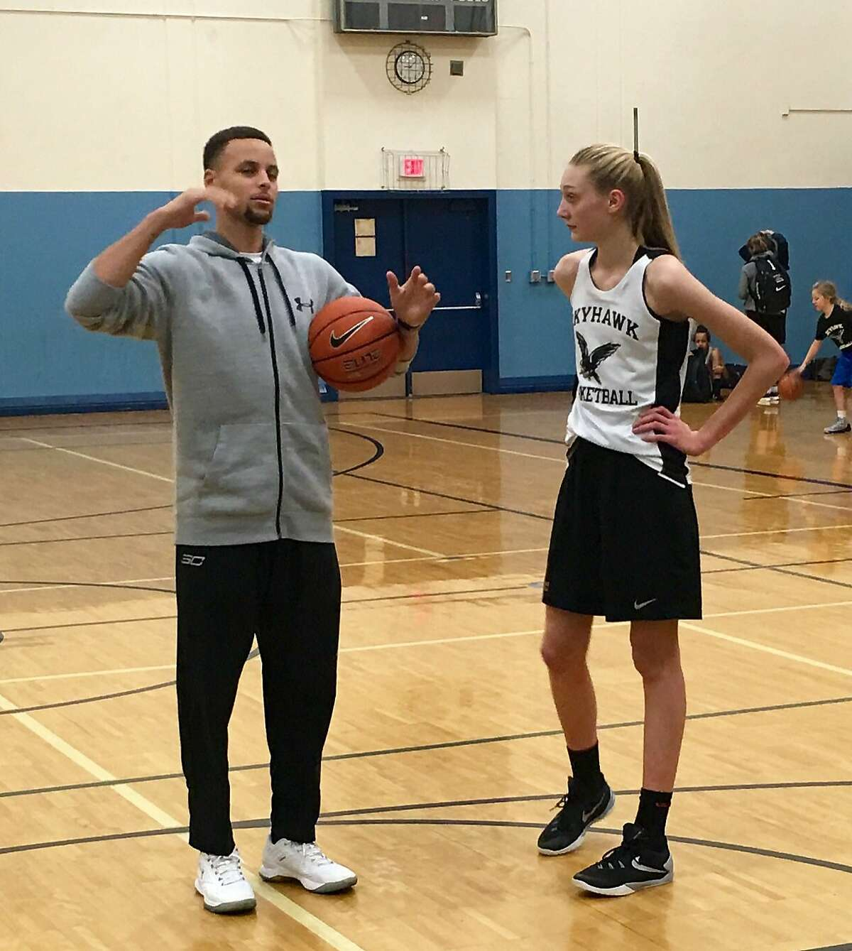 Stephen Curry offers pointers to Cameron Brink during a 2013 workout.