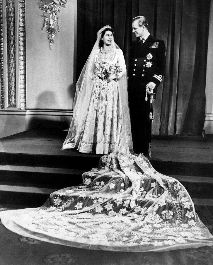 Princess Elizabeth and her husband Phillip, Duke of Edinburgh, at Buckingham Palace after their marriage at Westminster Abbey, 1947. Her gown was designed by Norman Hartnell.