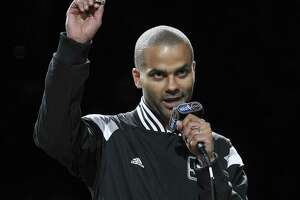 Spurs' Tony Parker holds up his 2014 NBA Championship ring during the ring ceremony and season opener against the Dallas Mavericks at the AT&T Center on Tuesday, Oct. 28, 2014. (Kin Man Hui/San Antonio Express-News)