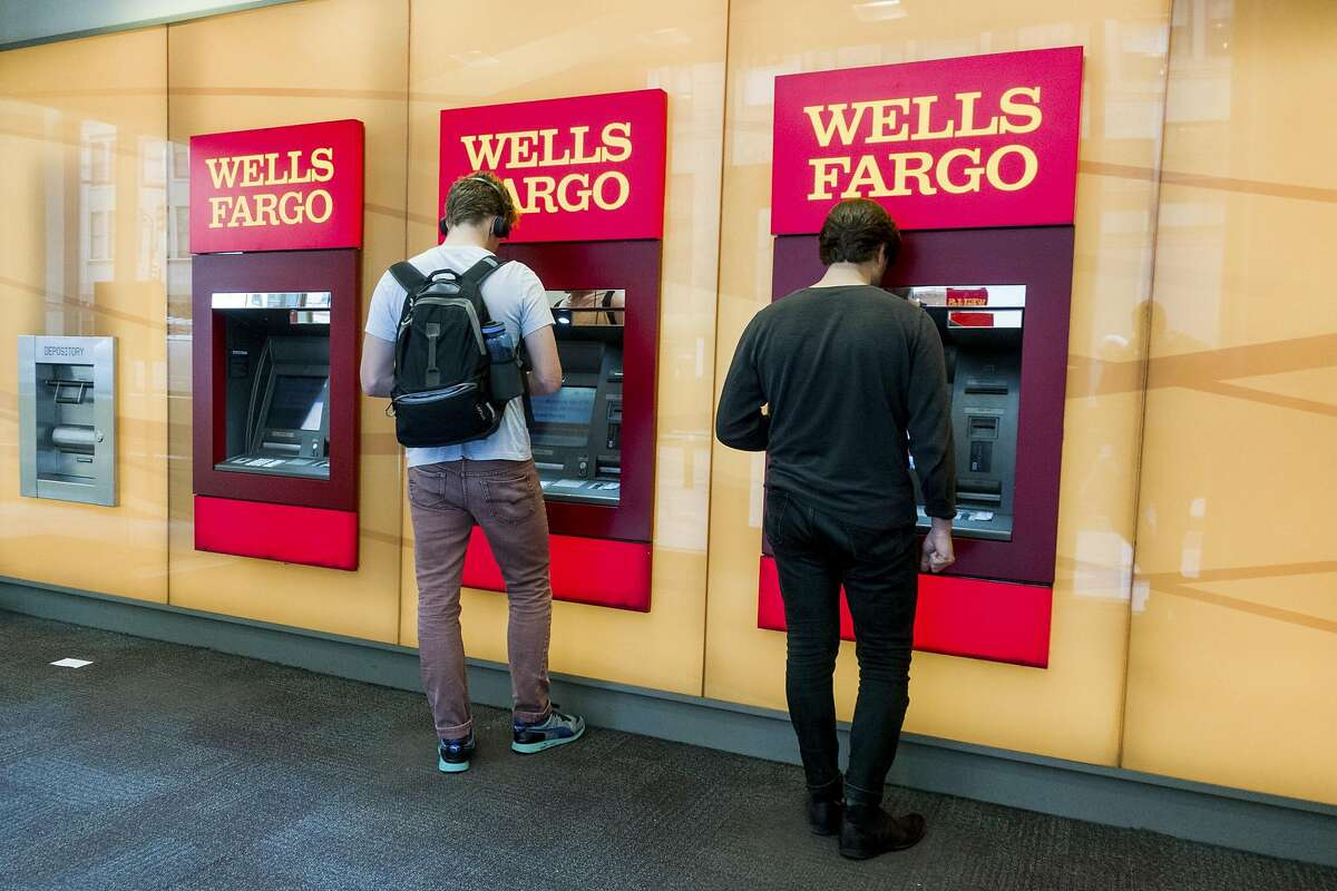 FILE - Patrons use ATMs at a Wells Fargo bank in New York, Sept. 7, 2017. Wells Fargo agreed to pay $575 million to resolve investigations by all 50 states and Washington, D.C., that began after federal regulators revealed in September 2016 that employees had for years opened millions of unauthorized bank accounts in customers' names. (Devin Yalkin/The New York Times)