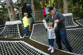 Midland residents Christopher Hockemeyer, right, and Brooke Stewart, 19 months, center, explore the Whiting Forest Canopy Walk during its opening day on Sunday, Oct. 7, 2018. (Katy Kildee/kkildee@mdn.net)