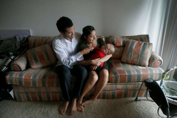 Justin Watson and his wife Citlali Gonzalez-Watson hold 6-month-old son Daniel at their new apartment in Milpitas, Calif. on Friday, Dec. 21, 2018.
