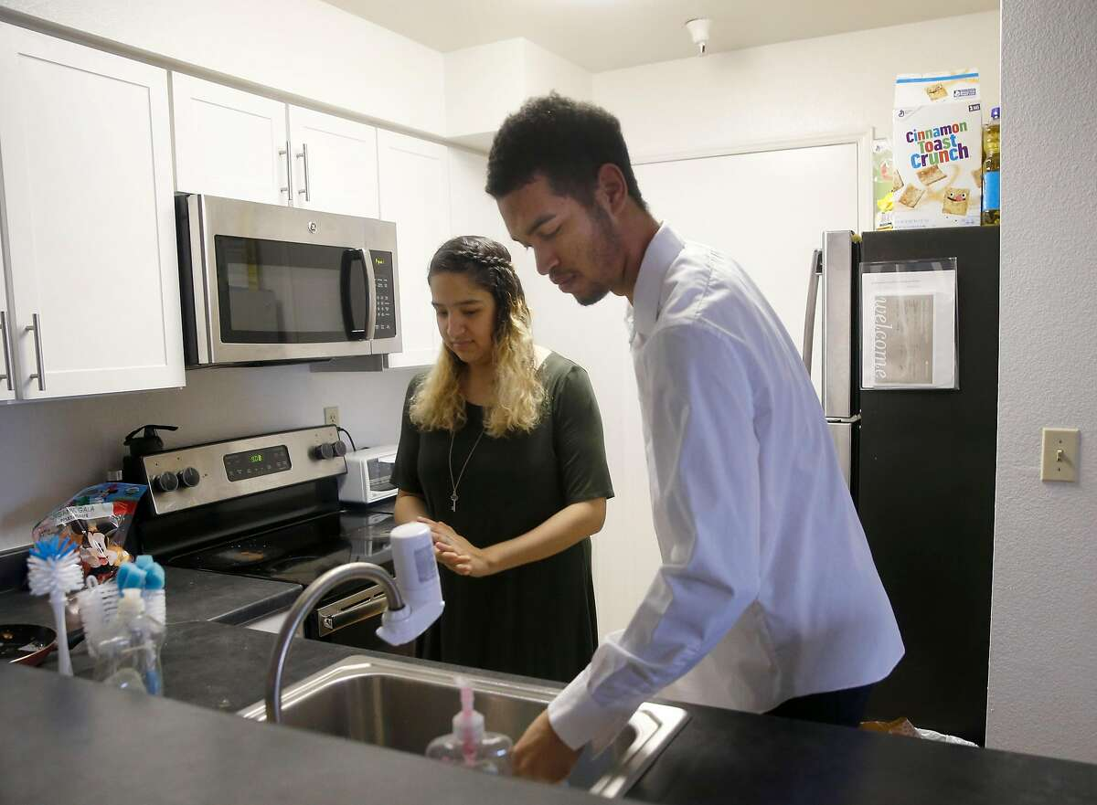 Justin Watson and his wife Citlali Gonzalez-Watson work in the kitchen at their new apartment in Milpitas, Calif. on Friday, Dec. 21, 2018.