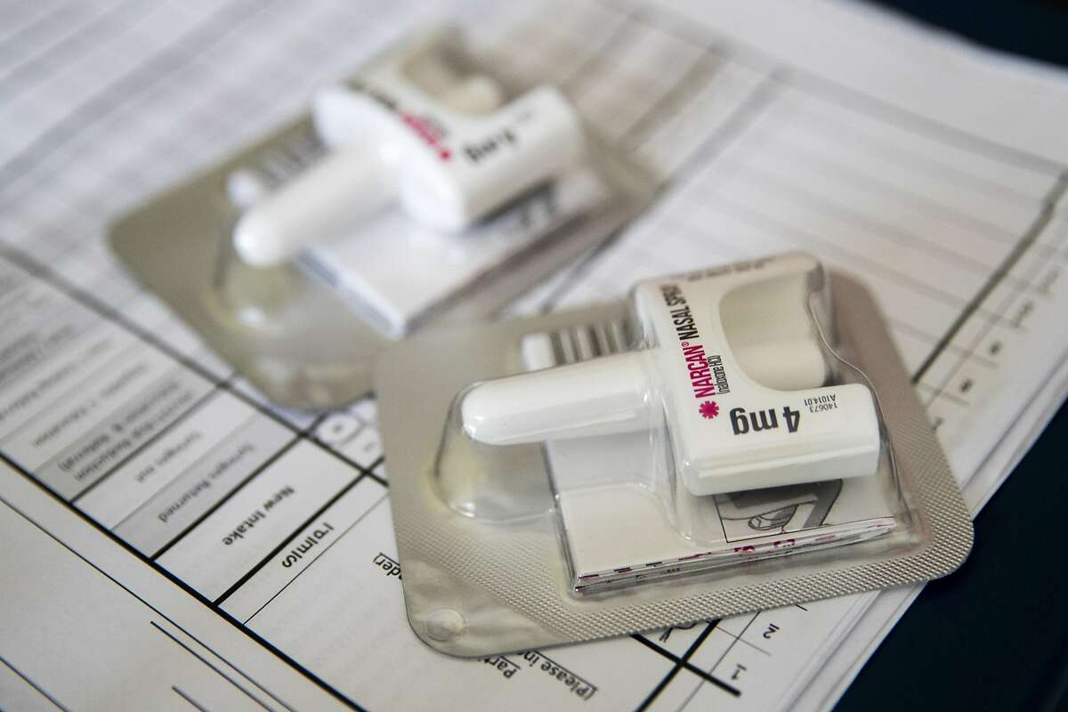 FILE - In this Tuesday, July 3, 2018 file photo, a Narcan nasal device which delivers naloxone lies on a counter as a health educator gives instructions on how to administer it in the Brooklyn borough of New York. On Wednesday, Dec. 19, 2018, the U.S. government told doctors to consider prescribing the overdose antidote naloxone to many more patients who take opioid painkillers. (AP Photo/Mary Altaffer)