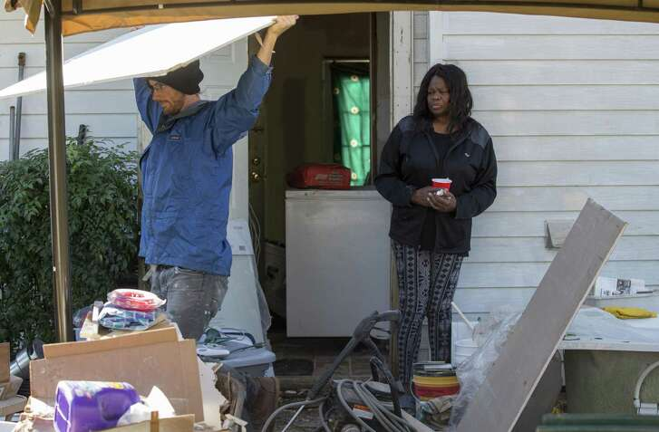 Ann Weston, right, stands in her backyard as Andrew Cobb, with West Street Recovery, moves sheetrock as the nonprofit works to fix the work done by the FEMA-funded Harvey home repair program known as PREPS Thursday, Dec. 20, 2018, in Houston.