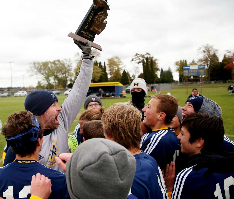 Bad Axe soccer coach Adam Sutherland holds up the Division 4 district soccer championship trophy for his players, after defeating Valley Lutheran, on a late Sunday afternoon, in Bad Axe. Photo: Tribune File Photo