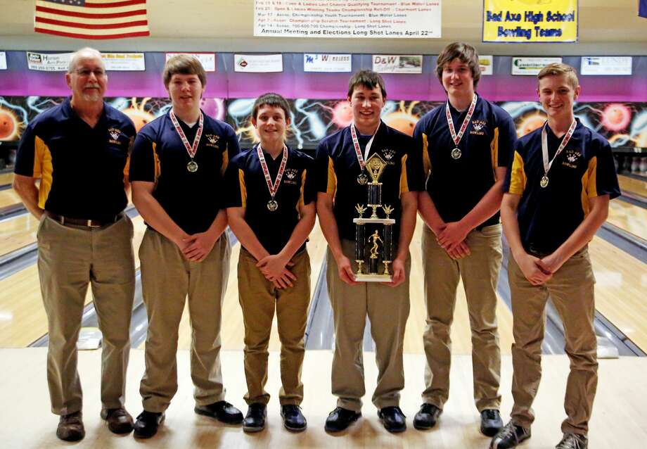 The Bad Axe bowling team poses with its conference trophy, after winning 316-315 championship match over Harbor Beach. The Hatchets needed three straight strikes to win the match, and Gavynn Guigar delivered. Photo: Tribune File Photo