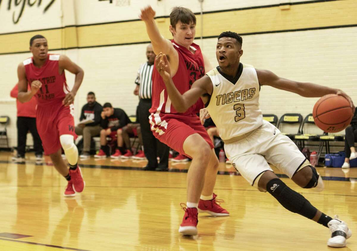 Michael Phoenix of Conroe (3) drives past Kia Peterson of Waltrip (32) during the 54th annual Conroe Christmas Classic on Friday, Dec. 28, 2018 at Conroe High School in Conroe.