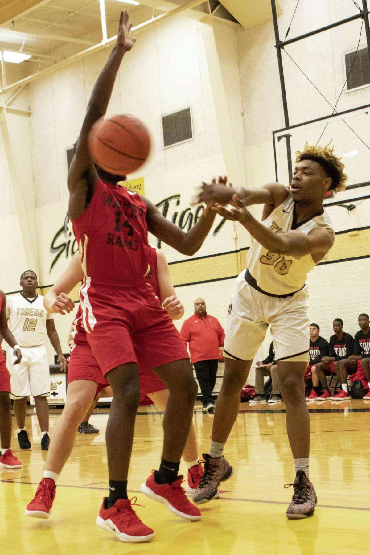 Keith Edmond of Conroe (30) passes the ball around Matthew Ceron of Waltrip (14) during the 54th annual Conroe Christmas Classic on Friday, Dec. 28, 2018 at Conroe High School in Conroe.