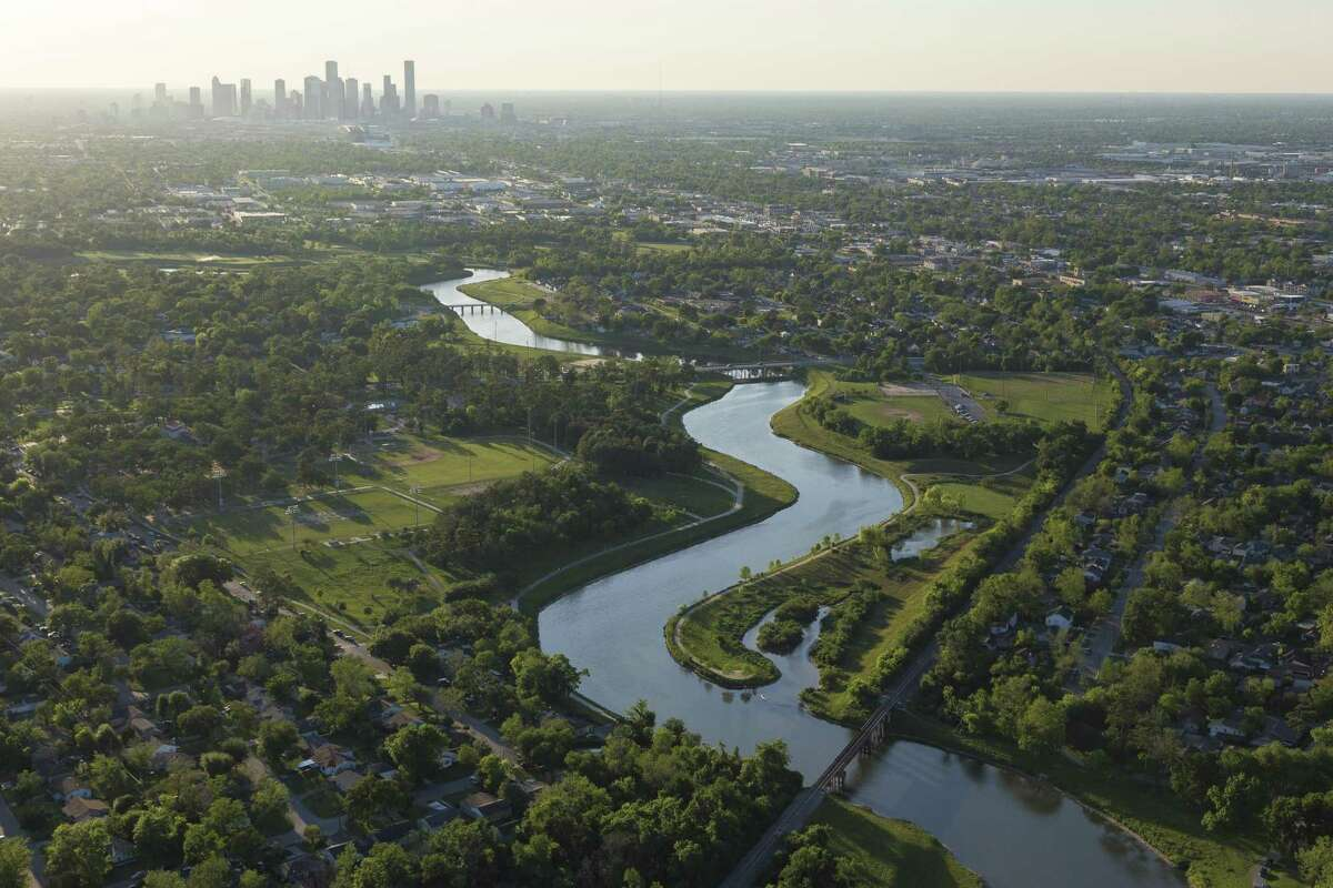 Houston skyline is seen with the Brays Bayou greenway in the forground.