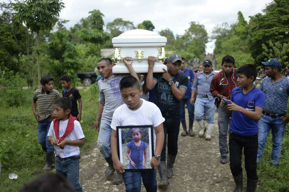 "A boy carries a picture of Guatemalan seven-year-old Jakelin Caal, who died in a Texas hospital two days after being taken into custody by US border patrol agents in a remote stretch of the New Mexico desert, as her coffin is taken from Raxruha to the cemetery in San Antonio Secortez, both villages in Alta Verapaz Department, 320 km north of Guatemala City, on December 25, 2018. - Jakelin Caal died after being arrested with her father and others crossing from Mexico into the US on December 6. Together they had travelled more than 3,000 km from their hometown of Raxruha, Guatemala. According to local media citing US Customs and Border Protection, the cause of death was ""dehydration and shock"". (Photo by Johan ORDONEZ / AFP)JOHAN ORDONEZ/AFP/Getty Images Photo: JOHAN ORDONEZ, Contributor / AFP/Getty Images / AFP or licensors"