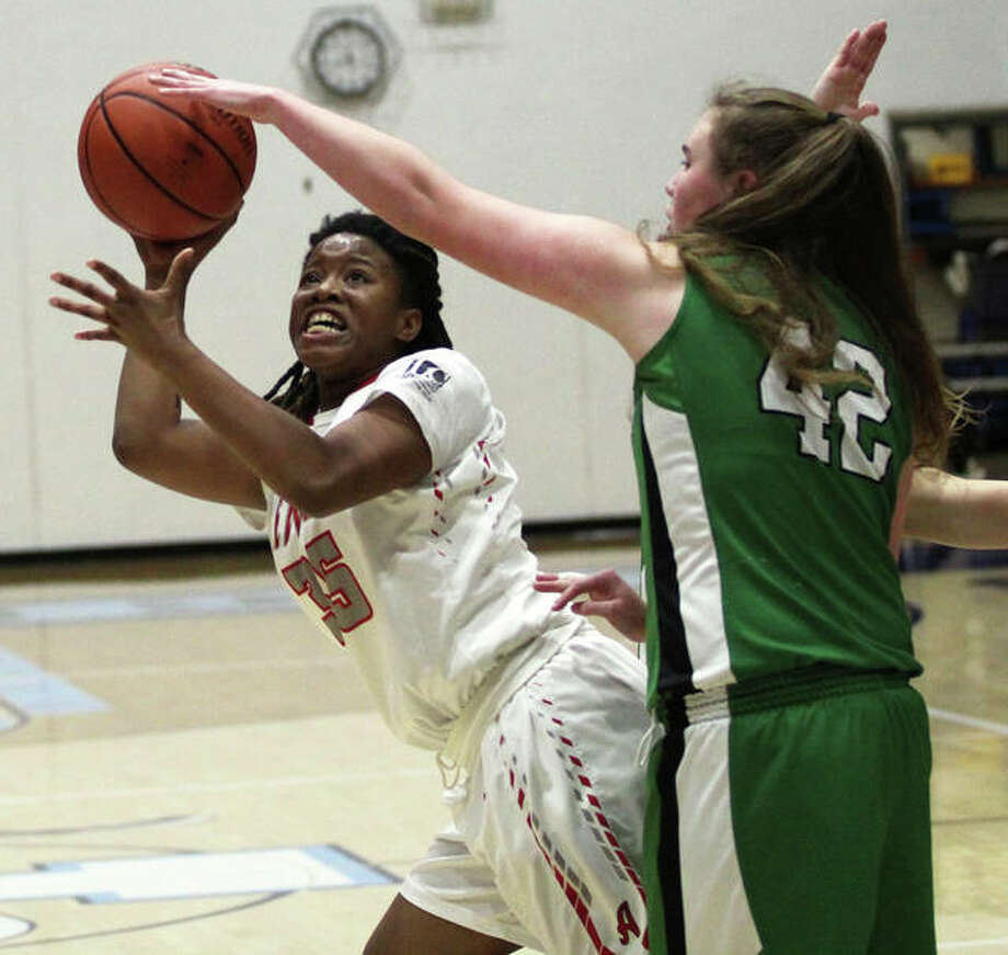 Alton's Hananiah Hamilton (left) scores on an off-balance shot in the lane after getting around Carrollton's Ava Uhles on Thursday at the Deck the Halls with Basketballs Tournament at Havens Gym in Jerseyville Photo: Greg Shashack / The Telegraph