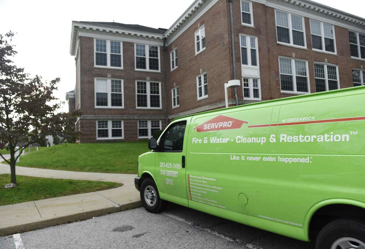 A maintenance van is parked outside Cos Cob School in the Cos Cob section of Greenwich, Conn. Tuesday, Oct. 9, 2018. A plumbing fixture broke over the weekend, causing damage to much of the first and second floor. The district will relocate at least three grades of students, kindergarteners, first and second graders, while students in grades 3, 4 and 5 will return to classes in the third floor of the school. Officials have not yet determined how long the clean-up and restoration will take to complete.