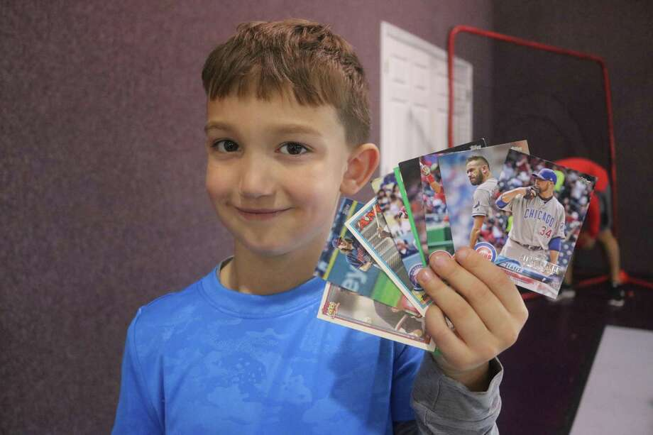 Braxton Landers displays the many baseball cards he received from the camp staff for his work at improving his hitting on Day 1 of the annual Holiday Baseball Camp Thursday. Photo: Robert Avery