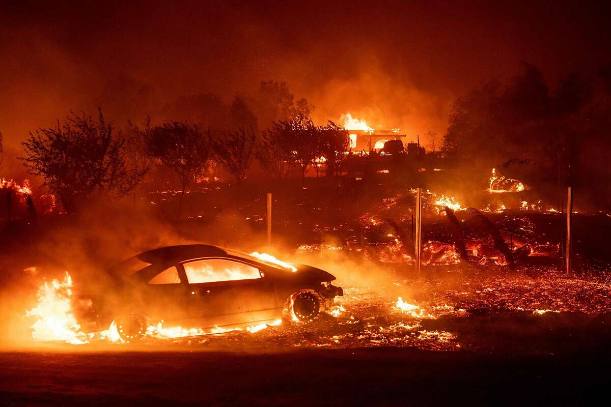 (FILES) In this file photo taken on November 8, 2018 Vehicles and homes burn as the Camp fire tears through Paradise, California. - The so-called Camp Fire broke out in early November 2018, in Butte County, killing at least 86 people and burning 14,000 homes in the tree-blanketed Sierra Nevada foothills of northern California. Insurance claims have already topped $7 billion, and officials estimate it will cost at least $3 billion just to clear the charred debris of homes and businesses. (Photo by Josh Edelson / AFP)JOSH EDELSON/AFP/Getty Images