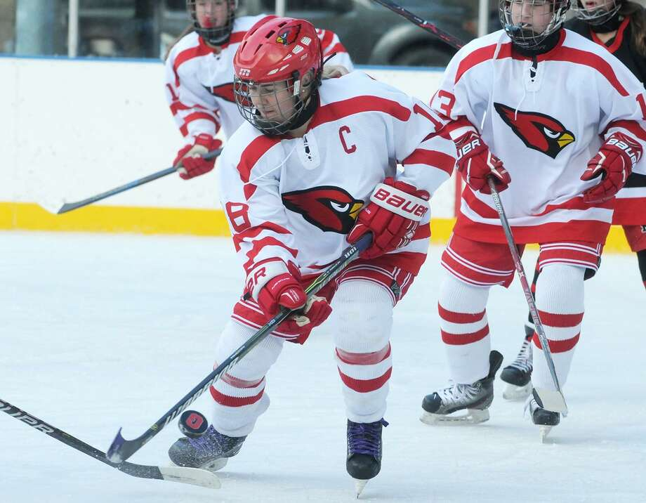 Greenwich senior co-captain Jennifer Kelly battles for the puck during the Cardinals' game with New Canaan in the Winter Classic at the Greenwich Skating Club on Saturday. Photo: Dave Stewart / Hearst Connecticut Media