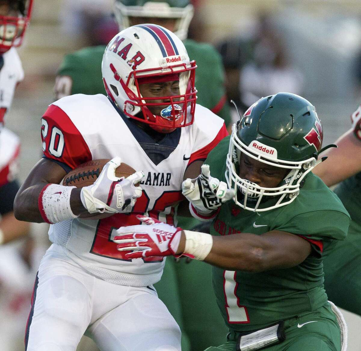 The Woodlands defensive back Austin Winfield (1) wraps up Lamar running back Cameron Kenner (20) during the first quarter of a non-district high school football game at Woodforest Bank Stadium on Thursday, Sept. 6, 2018, in Shenandoah.