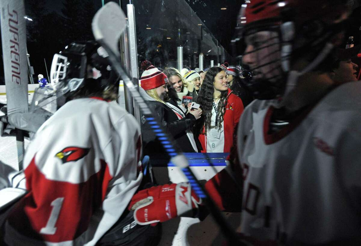 Katie Walko, Hallie Kretein and Lucy Fullton watch the Cardinals take to the ice during the Winter Classic Saturday, December 29, 2018, where the Greenwich High School Cardinals takes on the Darien Blue Wave in their boys hockey game at the Greenwich Skating Club in Greenwich, Conn.