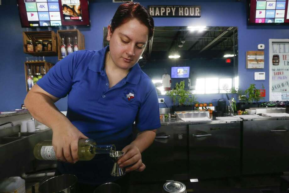 Bartender Kayla Van De Flier pours a drink at Texas Tail Distillery's Seawall Boulevard location on Saturday, Dec. 29, 2018, in Galveston. Texas Tail distills moonshine in a variety of flavors. It is an offshoot of Texas Tail vodka, which Greg Truex and partner Nick Droege started in Dallas in 2007. Photo: Brett Coomer, Houston Chronicle / Staff Photographer / © 2018 Houston Chronicle