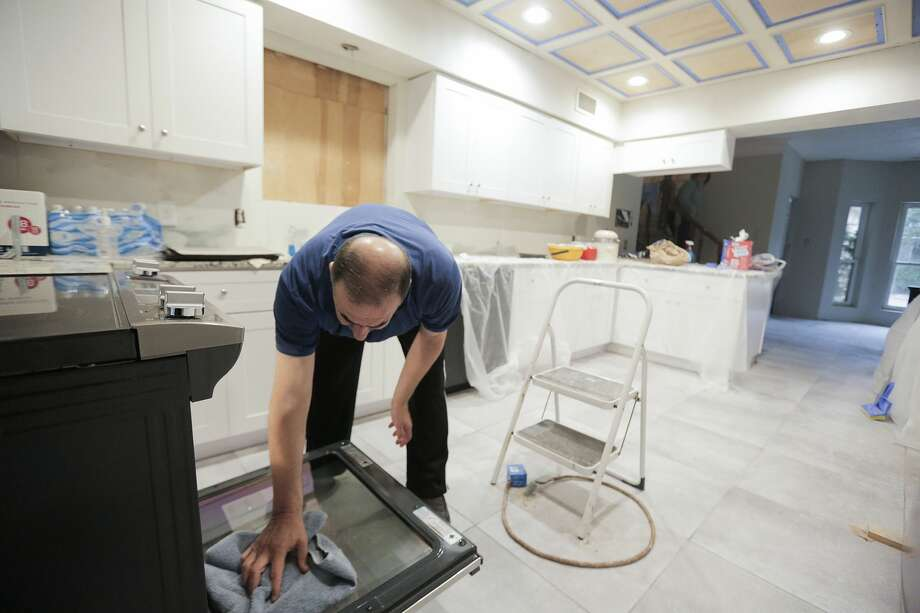 Victor Khoury works on dinner in an unfinished kitchen in his home in December 2018. Before Harvey their bedroom was on the first floor of their 6000 sq ft home. Now they are living on the second floor, mostly above the garage as they try to repair their home. >>>See aerial photos of the damage wrought by Hurricane Harvey in the photos that follow... Photo: Elizabeth Conley/Staff Photographer