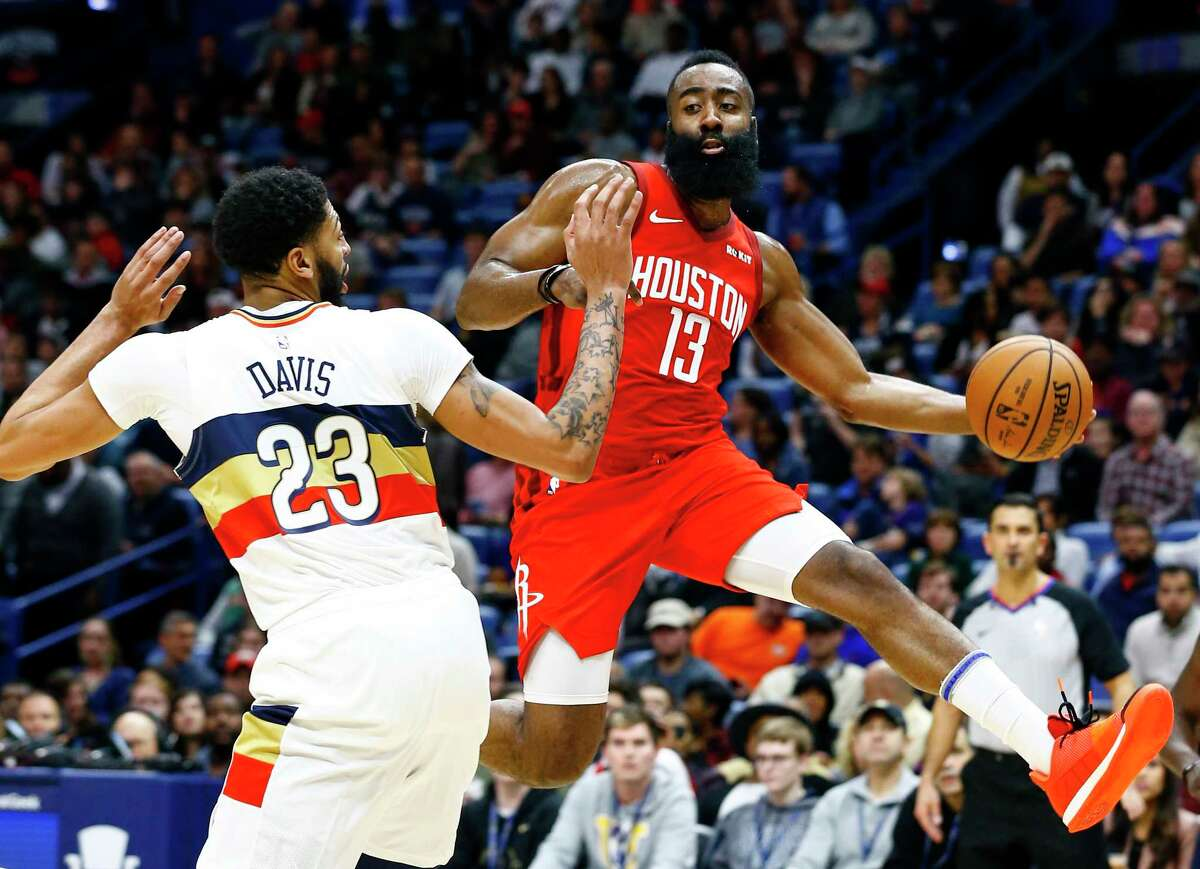 Houston Rockets guard James Harden (13) passes the ball around New Orleans Pelicans forward Anthony Davis (23) during the first half of an NBA basketball game, Saturday, Dec. 29, 2018, in New Orleans. (AP Photo/Butch Dill)
