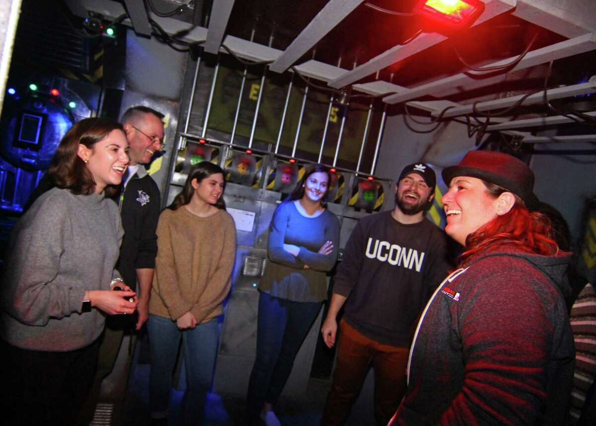 Escape Rooms Connecticut owner Michelle Mateus, right, talks to participants who just completed one of the escape rooms at their facility in Orange, Conn., on Saturday Dec. 29, 2018. Escape room adventures provide players the thrill of solving mysteries with clues on hand inside each room. Escape Rooms CT has three rooms with plans to add another one in the near future.