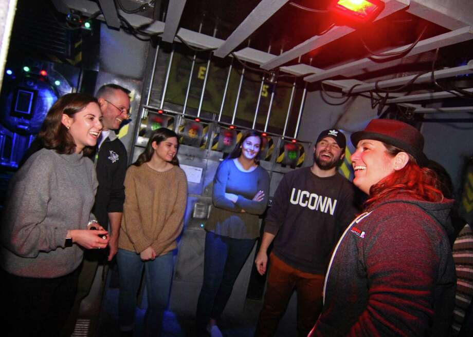 Escape Rooms Connecticut owner Michelle Mateus, right, talks to participants who just completed one of the escape rooms at their facility in Orange, Conn., on Saturday Dec. 29, 2018. Escape room adventures provide players the thrill of solving mysteries with clues on hand inside each room. Escape Rooms CT has three rooms with plans to add another one in the near future. Photo: Christian Abraham, Hearst Connecticut Media / Connecticut Post
