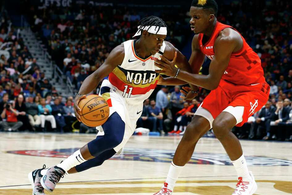 New Orleans Pelicans guard Jrue Holiday (11) drives to the basket around Houston Rockets center Clint Capela (15) during the second half of an NBA basketball game, Saturday, Dec. 29, 2018, in New Orleans. (AP Photo/Butch Dill)