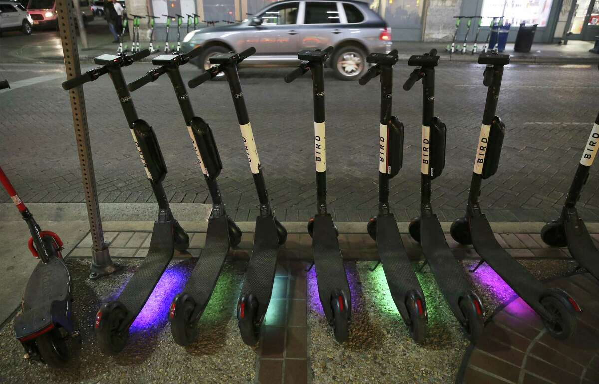 LED lights colorfully shine on a row of scooters in downtown San Antonio on Tuesday, Dec. 4, 2018. Scooters have rapidly made their presence felt in downtown San Antonio. For many users, the vehicle is a novelty and a handy method of transportation. But with the climbing growth of users, rules for their usage have been sketchy or unclear. Some users have gone as far as using them along the RiverWalk which is prohibited by the city. (Kin Man Hui/San Antonio Express-News)