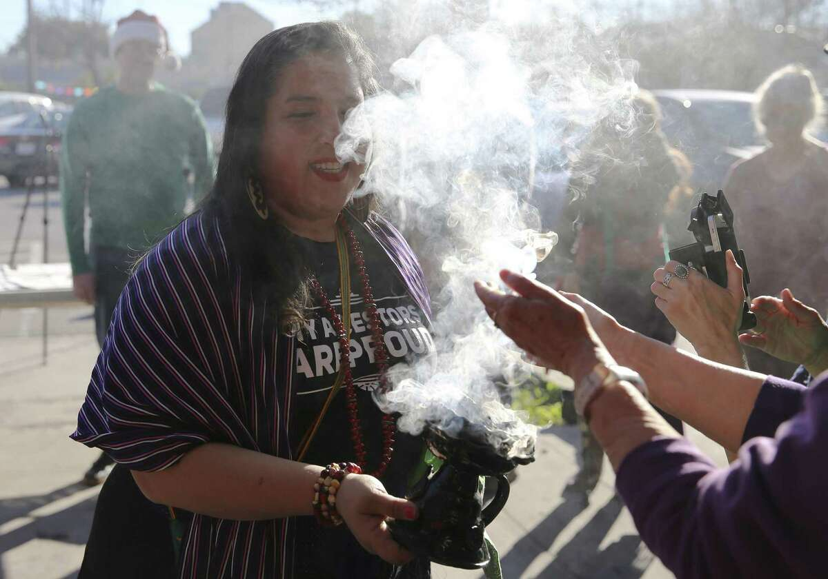 Karla Aguilar performs a cleansing ceremony as the Sierra Club holds a press conference and a gathering with other organizations to celebrate the closing of the coal-fired J.T. Deely power plant on Saturday, Dec. 15, 2018. The plant was the first in CPS Energy's fleet to burn coal and is being closed years earlier than originally planned.