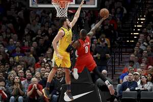 Portland Trail Blazers guard Damian Lillard, right, puts up a shot on Golden State Warriors guard Klay Thompson, left during the first half of an NBA basketball game in Portland, Ore., Saturday, Dec. 29, 2018. (AP Photo/Steve Dykes)