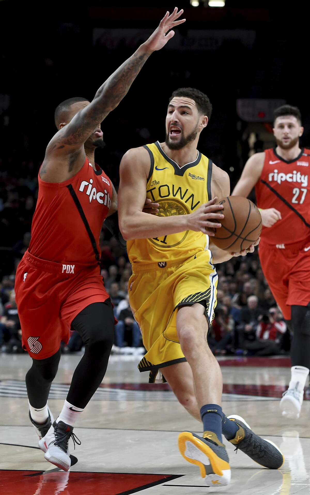 Golden State Warriors guard Klay Thompson, right, drives to the basket on Portland Trail Blazers guard Damian Lillard, left, during the first half of an NBA basketball game in Portland, Ore., Saturday, Dec. 29, 2018. (AP Photo/Steve Dykes)