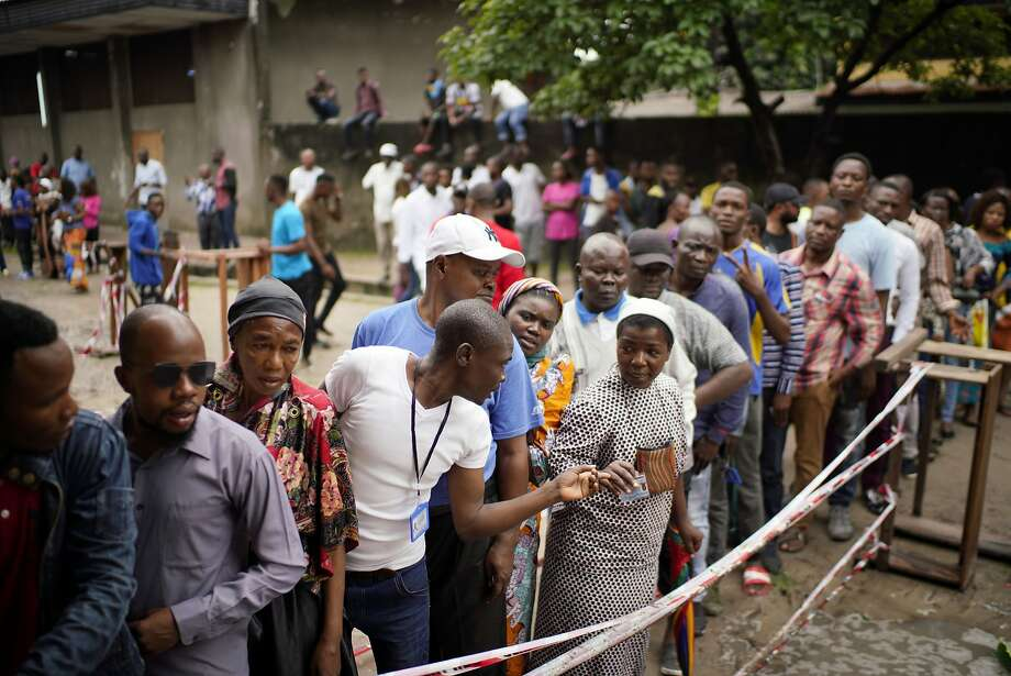 Congolese line up to vote in Kinshasa after the listings were finally posted, five hours after the official start of voting. Photo: Jerome Delay / Associated Press