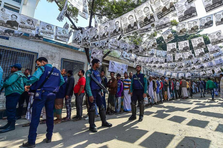 Officers guard a polling station adorned with campaign posters in Dhaka as voters wait in line. Prime Minister Sheikh Hasina won a third consecutive term despite allegations of intimidation. Photo: Munir Uz Zaman / AFP / Getty Images