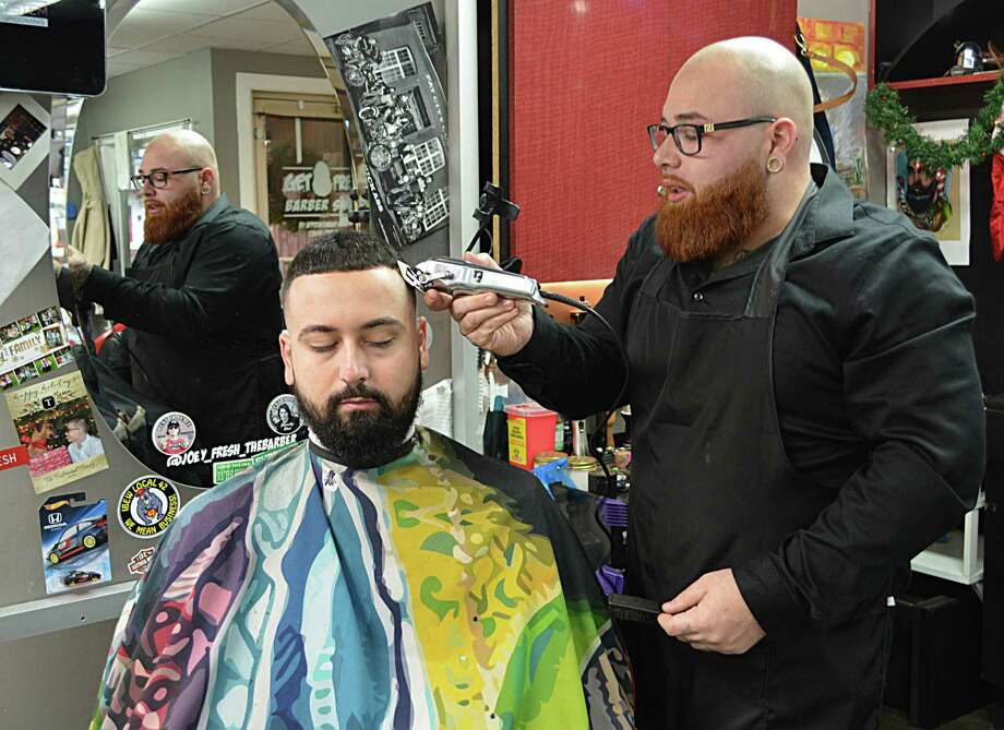 Joey Pelkey, 26, owner of Get Fresh Barber Shop at 131 Saybrook Road in Middletown, has been named The Middletown Press' Person of the Year for 2018. Here, Pelkey gives barber Kyle Whitty a trim Friday morning in between customers. Photo: Cassandra Day / Hearst Connecticut Media