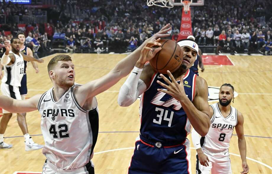 San Antonio Spurs forward Davis Bertans, left, reaches for a rebound as Los Angeles Clippers forward Tobias Harris grabs it while guard Patty Mills, right, watches during the first half of an NBA basketball game Saturday, Dec. 29, 2018, in Los Angeles. (AP Photo/Mark J. Terrill) Photo: Mark J. Terrill/Associated Press