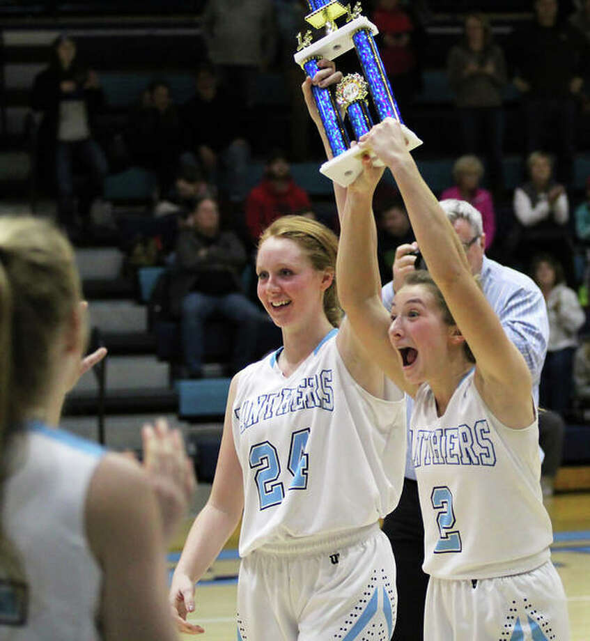 Jersey seniors Brooke Tuttle (right) and Hannah Hudson raise the championship trophy overhead and deliver it to teammates Saturday night after winning the Deck the Halls with Basketballs Tournament at Havens Gym in Jerseyille. It was the Panthers' first tourney title in 18 years. Photo: Greg Shashack / The Telegraph
