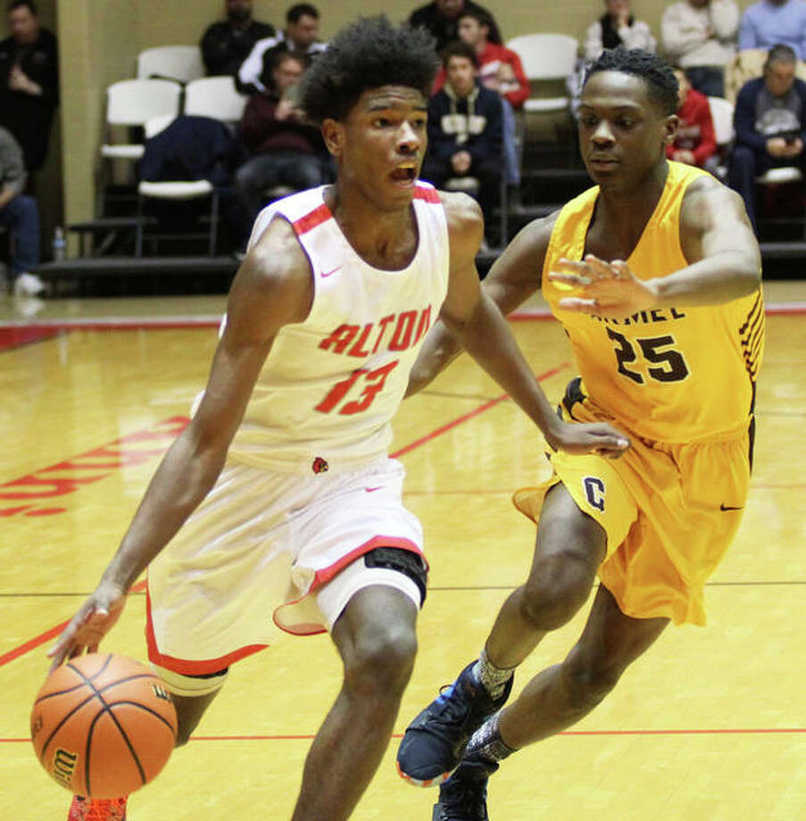 Alton's Malik Smith (left) drives past Mundelein-Carmel's Bryce Moore during the Redbirds quarterfinal win Friday at the Centralia Holiday Tournament at Trout Arena. Smith scored a team-high 16 points in Saturday night's title-game loss to Belleville West. Photo: Greg Shashack / The Telegraph